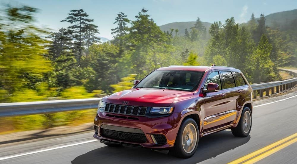 A red 2019 Jeep Grand Cherokee is shown driving down a highway with trees and mountains in the background near a Jeep dealership in Dallas, TX.