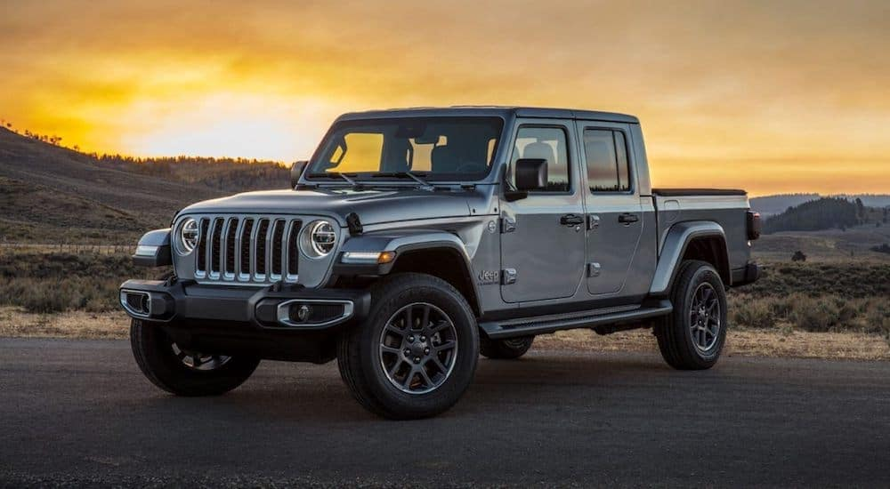 A grey 2020 Jeep Gladiator is parked on the side of a hill with a yellow sunset sky in the background.