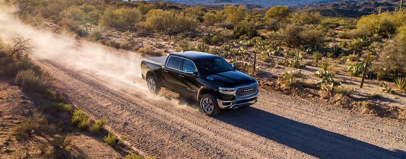 A black 2019 RAM 1500 is driving fast on a desert dirt road.