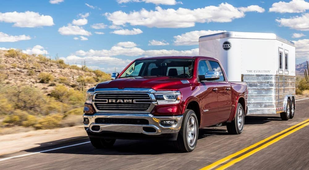 A red 2019 RAM 1500, popular among RAM trucks, is towing a white trailer.