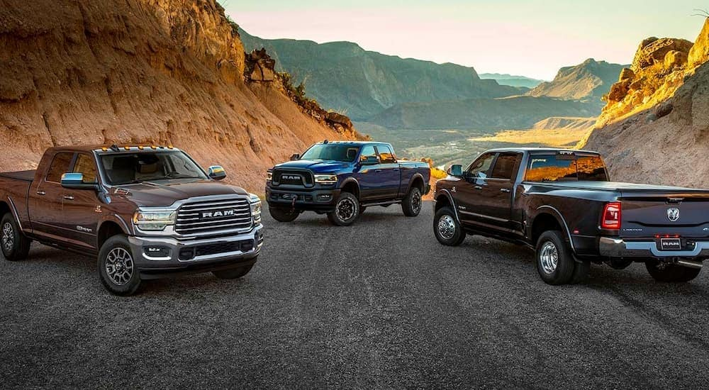 Three 2019 RAM 2500 trucks are parked on a desert road with hills.