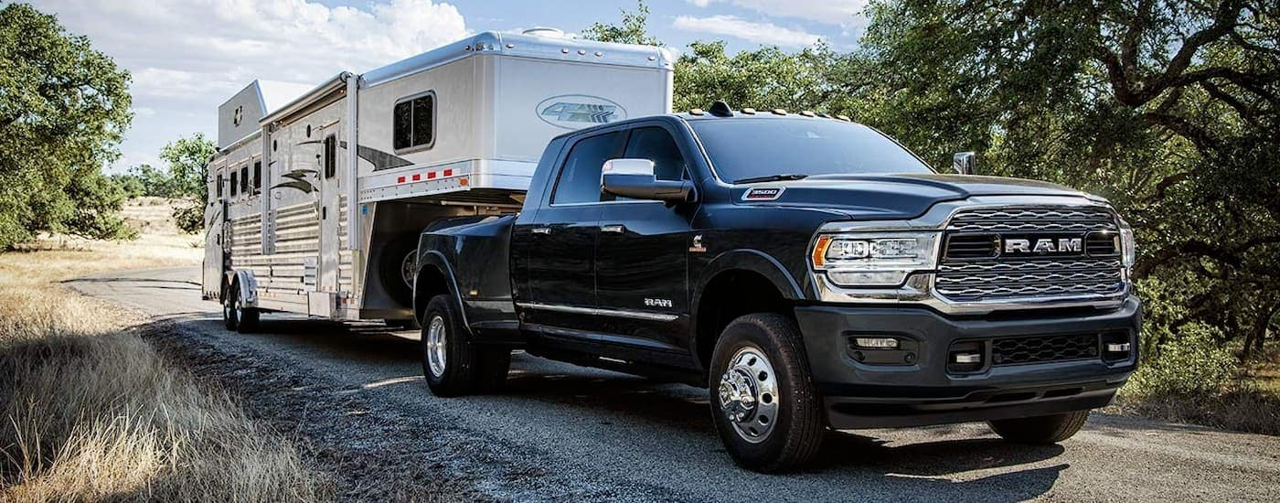 A black 2019 RAM 3500 is towing a large horse trailer on a dirt road near Ennis, TX.