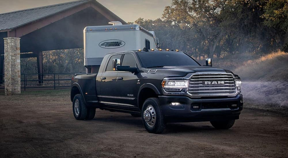 A black 2019 RAM 3500 is parked on an Ennis, TX farm with a trailer.