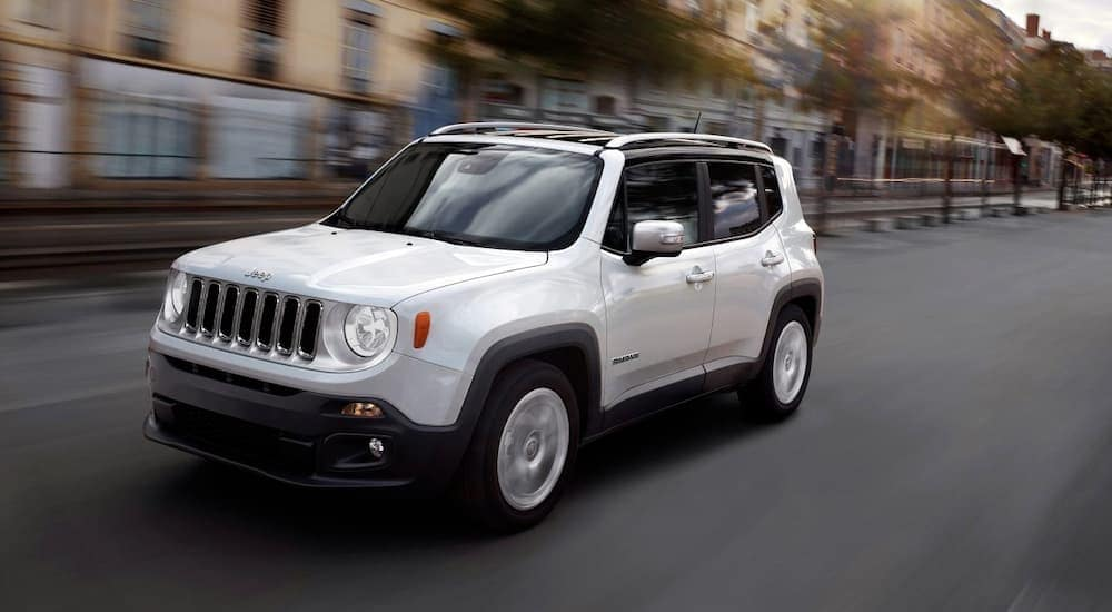 A white 2018 Jeep Renegade, popular among used cars near me, is driving past blurred buildings.