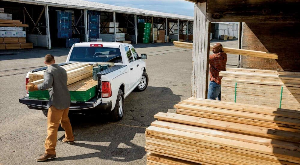 Two men are loading wood into a white 2018 Ram 1500 at a lumber yard.