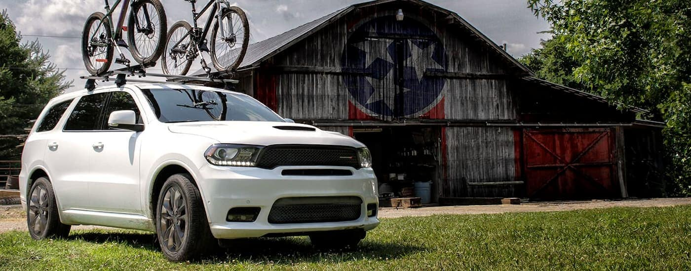 A white 2019 Dodge Durango with bikes on the roof is parked next to a patriotic barn near Ennis, TX.