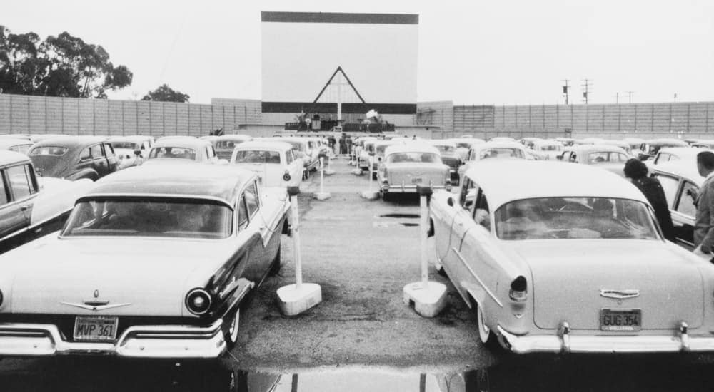 A black and white image is shown of classic cars at a drive-in theater.