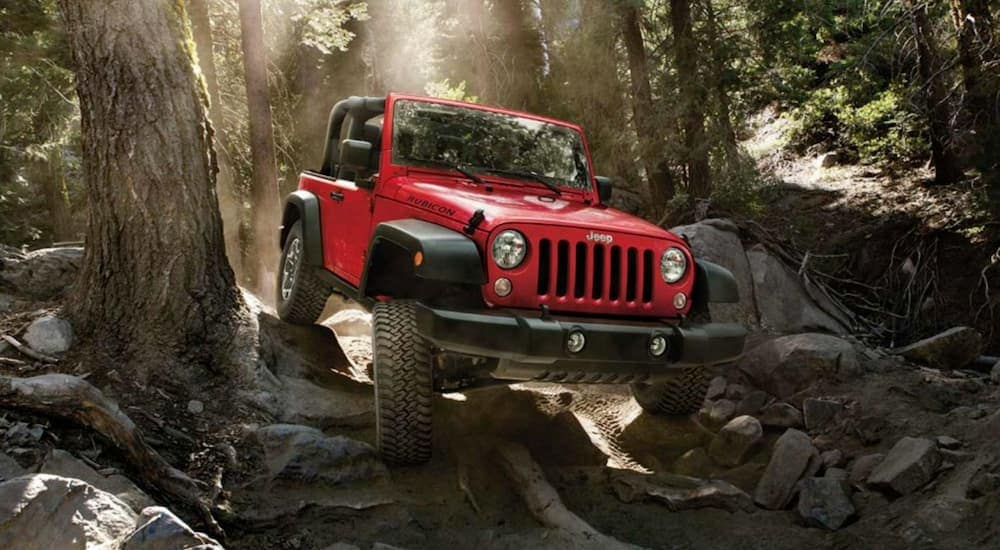 A red 2016 used Jeep Wrangler for sale is on a rocky trail outside Ennis, TX.