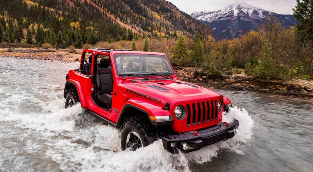 A red 2018 Jeep Wrangler is driving through a river.