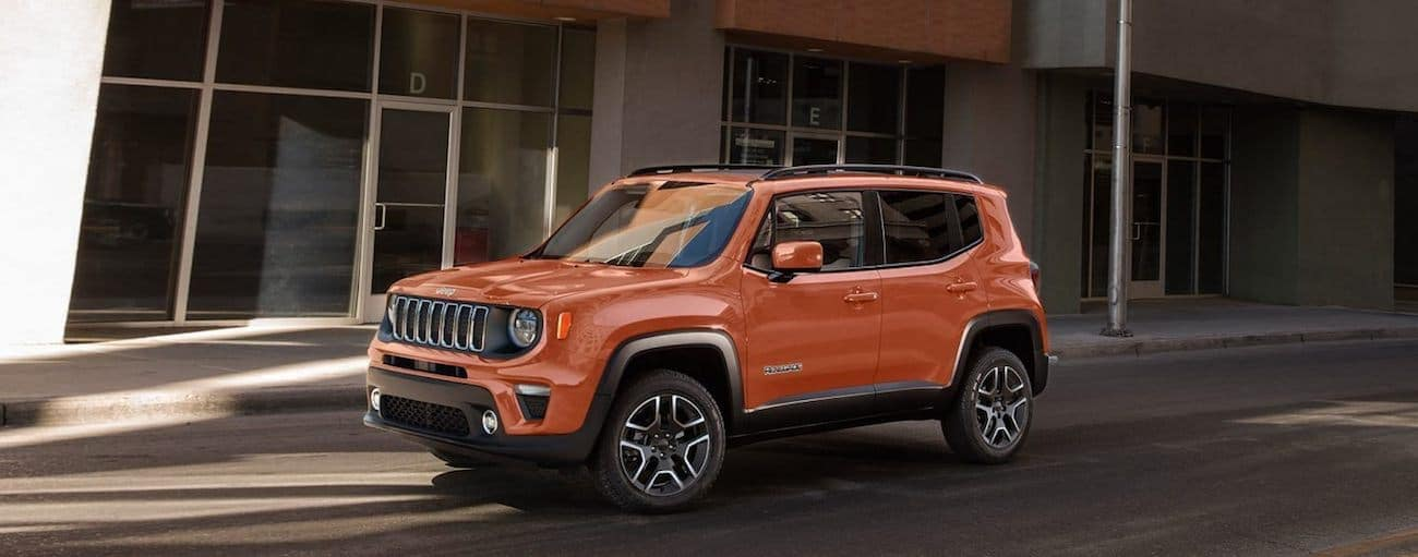 A side view of an orange 2020 Jeep Renegade is parked in front of an office building near Ennis, TX.