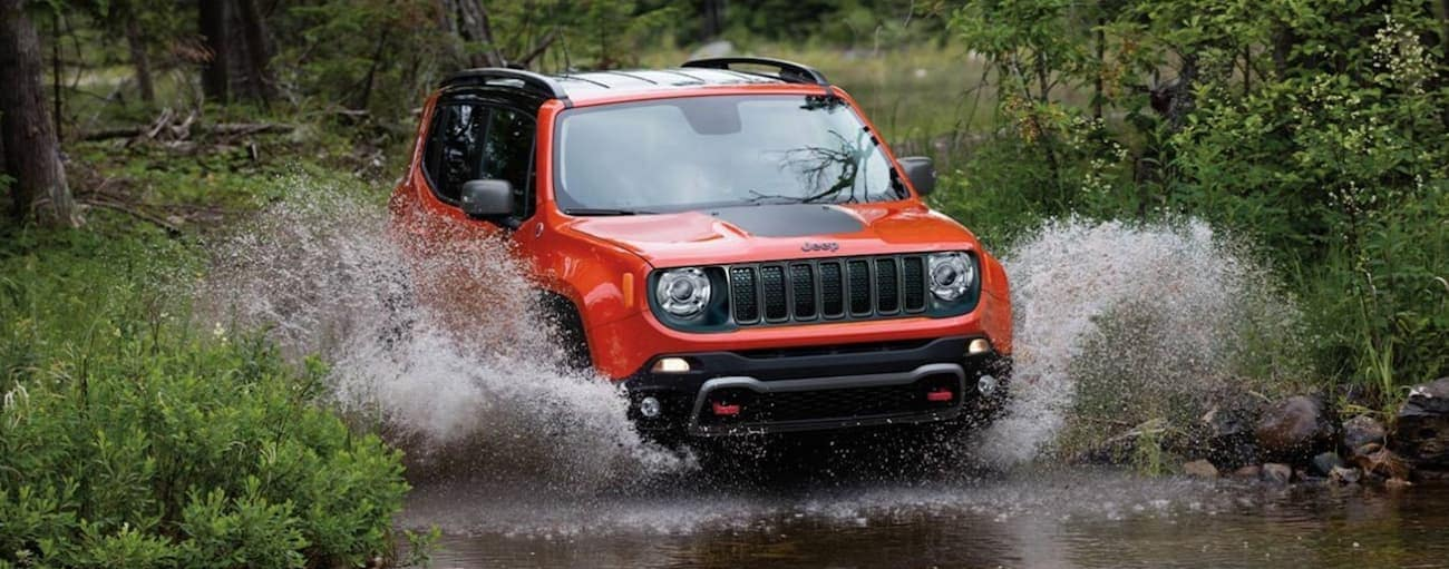 A red 2020 Jeep Renegade, which wins when comparing the 2020 Jeep Renegade vs 2020 Hyundai Kona, is driving through a river with water splashing up near Ennis, TX.
