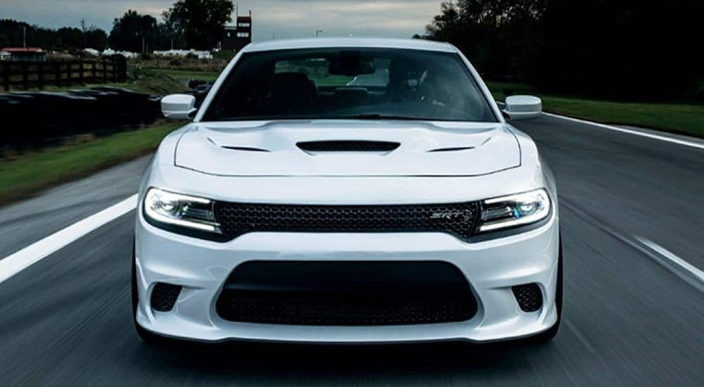 A white 2020 Dodge Charger SRT is driving on a paved street with dark storm clouds behind it.