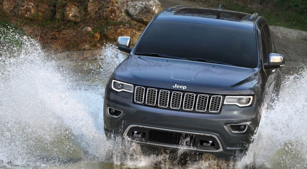 A grey 2019 Jeep Grand Cherokee, popular at a used car dealerships, is driving through a puddle near Ennis, TX.