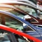 A row of used cars are shown at a used car dealership.