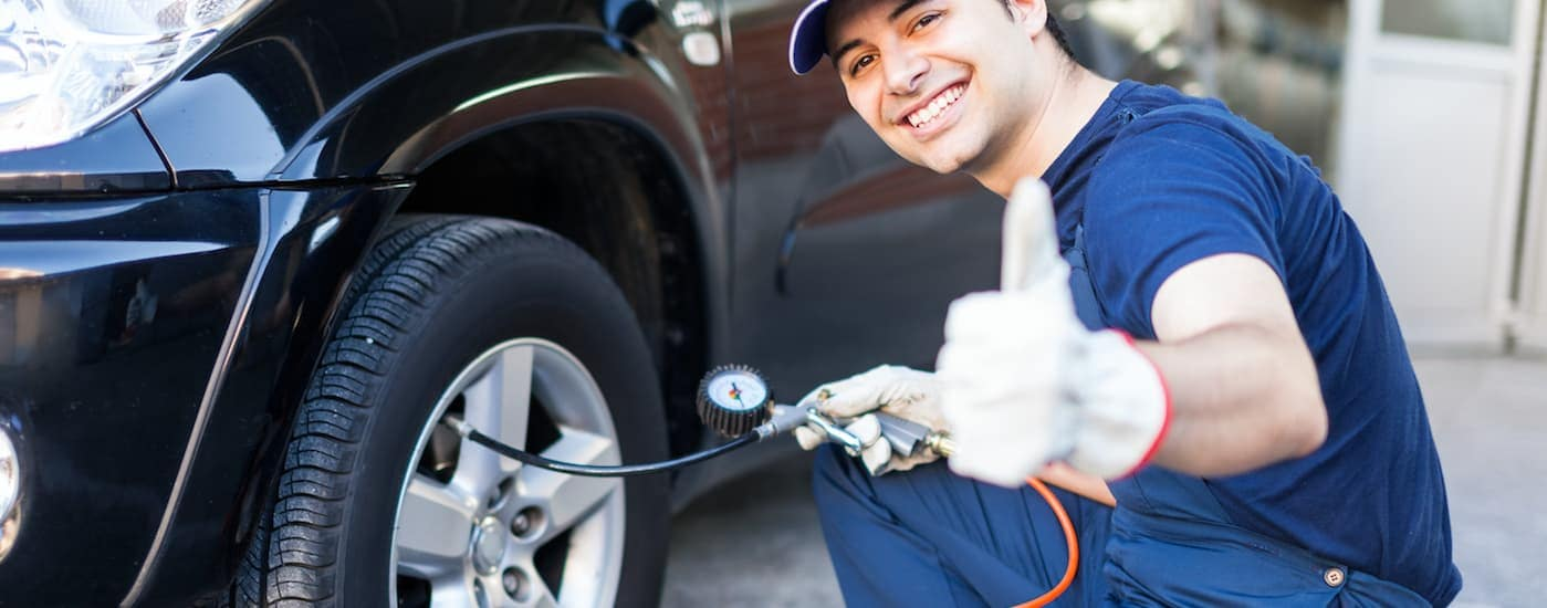 A mechanic is smiling and giving the thumbs up while checking a customer's tire pressure, which is a task that our shop can do when you search 'tire shop near me in Ennis, TX'.