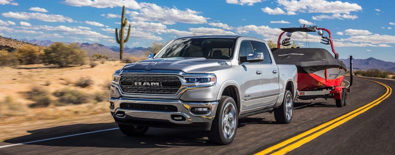 A silver 2020 Ram 1500, which wins when comparing the 2020 Ram 1500 vs 2019 Ram 1500 Classic, is towing a large boat near Ennis, TX.