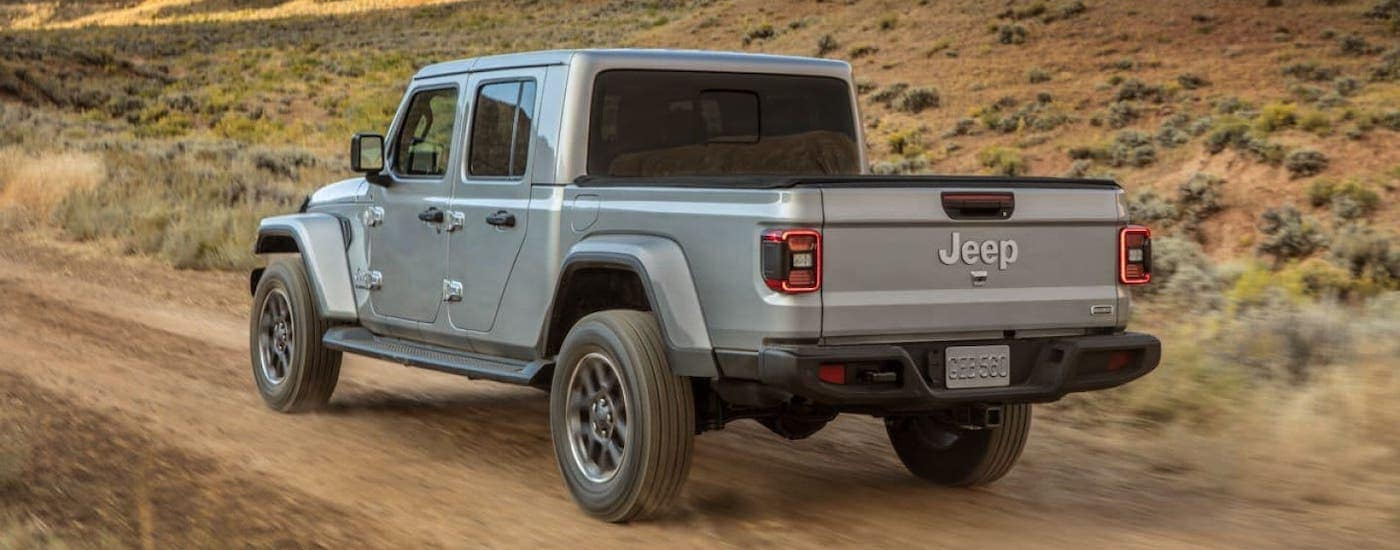 A silver 2020 Jeep Gladiator drives on a dirt road in a desert outside Ennis TX.