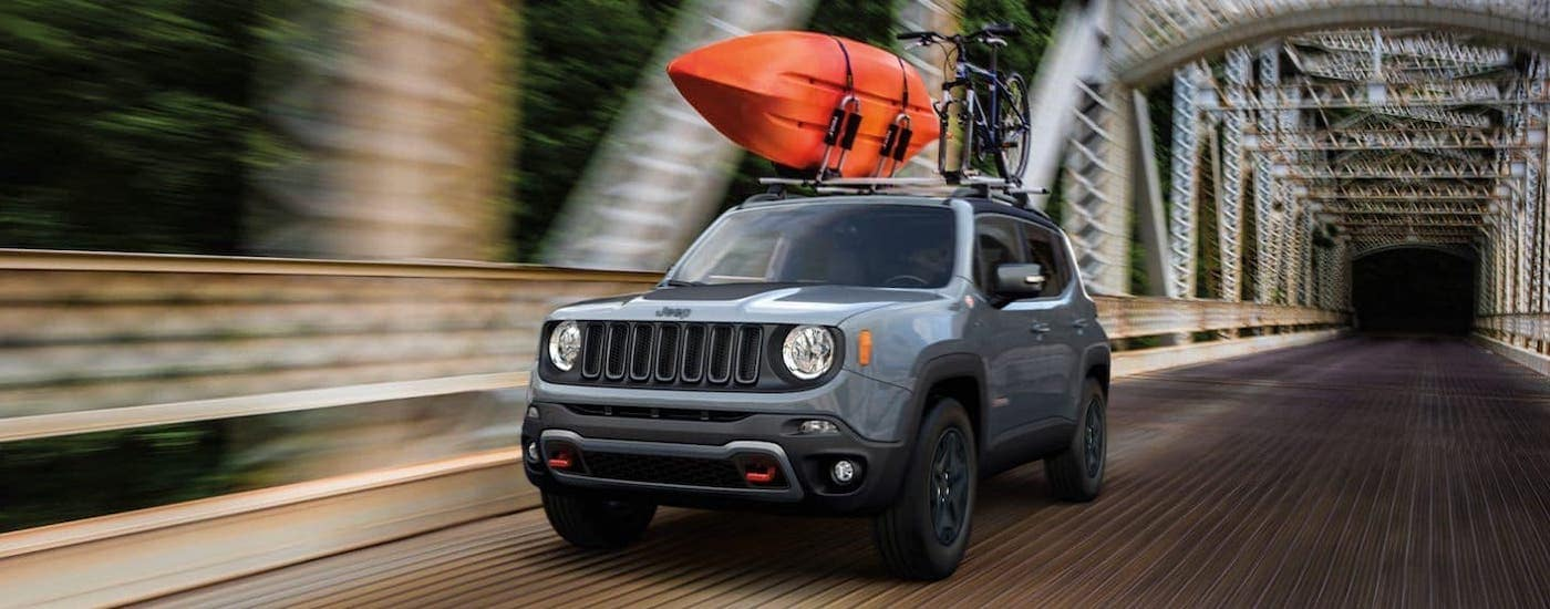 A gray 2020 Jeep Renegade carrying a kayak and bike driving over a rusty bridge.