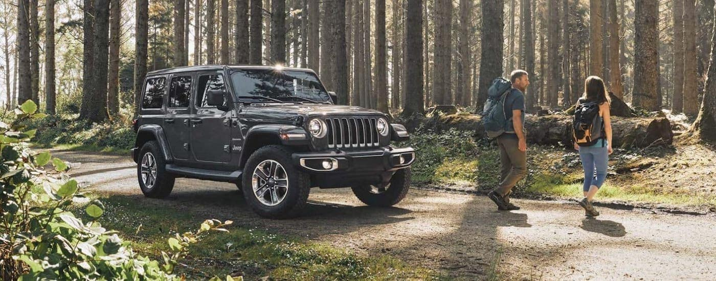 Two hikers walk away from a gray 2020 Jeep Wrangler Ultimate in a forest.
