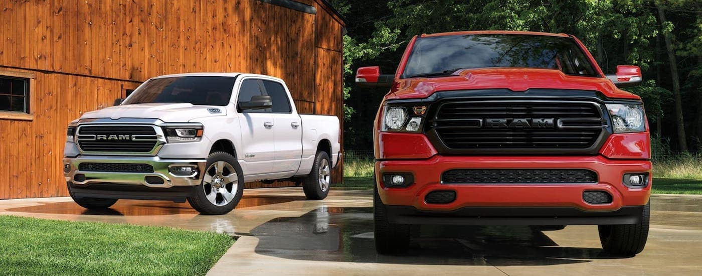 A red and a white 2020 Ram 1500s are parked in front of a barn outside Ennis, TX.