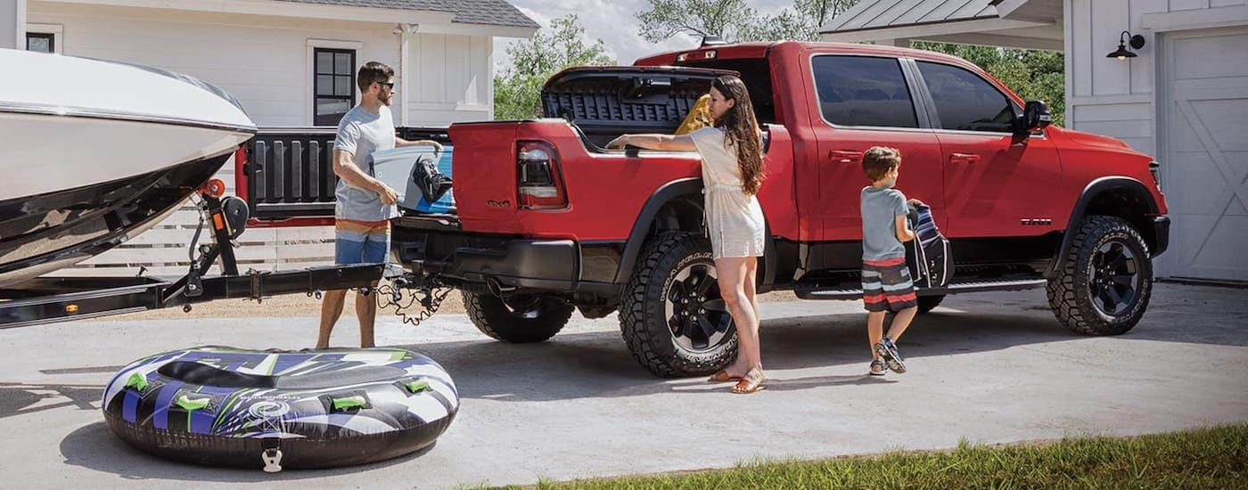 A family is getting ready for a boat tubing trip by loading a red 2020 Ram 1500.