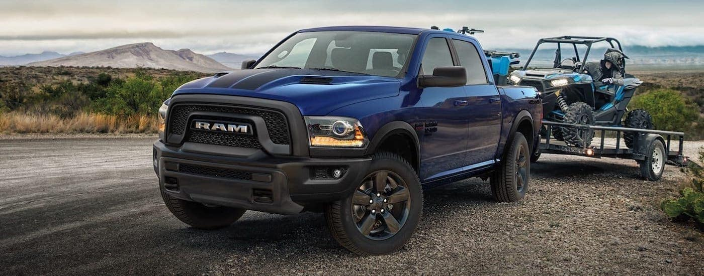 A blue 2020 Ram 1500 Classic Warlock with black racing stripes is unloading a trailer carrying a side by side on the side of a dirt road.