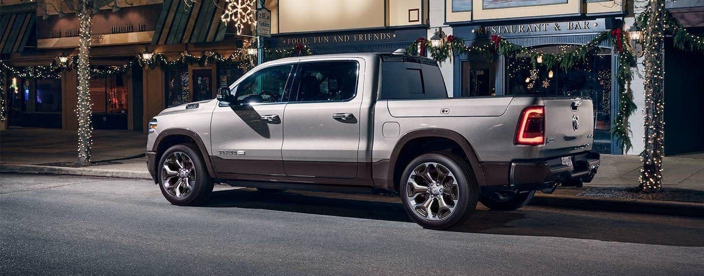 A silver 2020 Ram 1500 Laramie Longhorn is parked on a city street, see one at your local Ram Dealership in Ennis, TX.