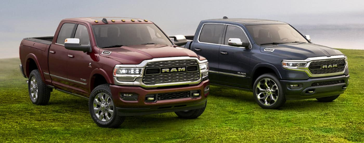 A red 2020 Ram 2500 is next to a blue 2020 Ram 1500, parked on grass.