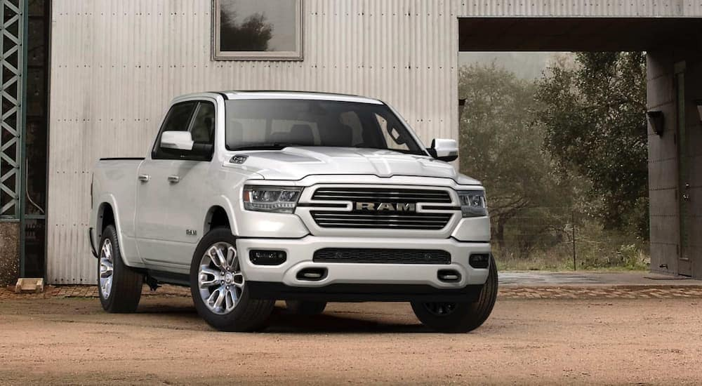A white 2020 Ram 1500 is parked in front of a white barn near Ennis, TX.