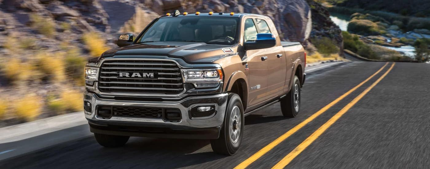 A brown 2020 Ram 2500 is driving on a mountain road after leaving a Ram dealer near me.