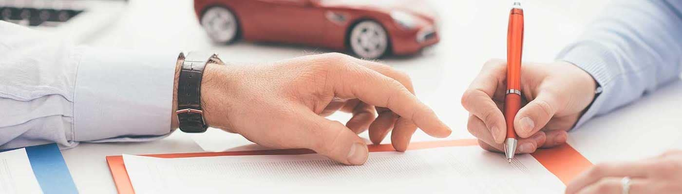 woman signing a document at a car dealership