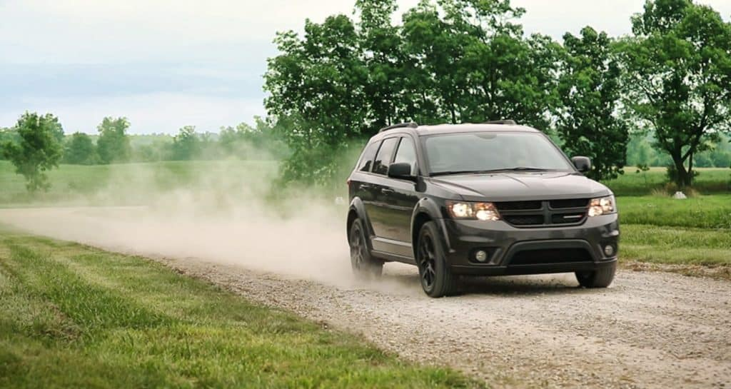 Dodge Journey SUV in black stirring up dust cloud while driving on dusty road.