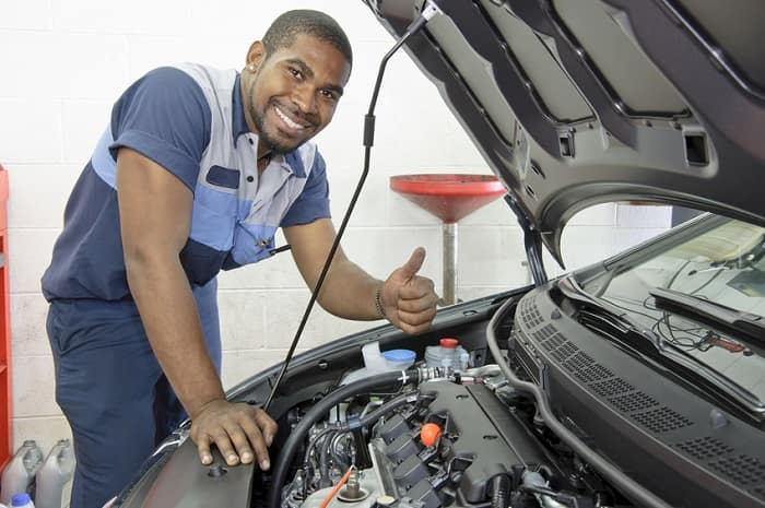 Auto technician inspecting a used car's engine in a garage.