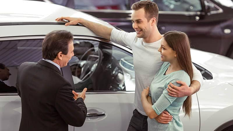 Couple talking with car salesman