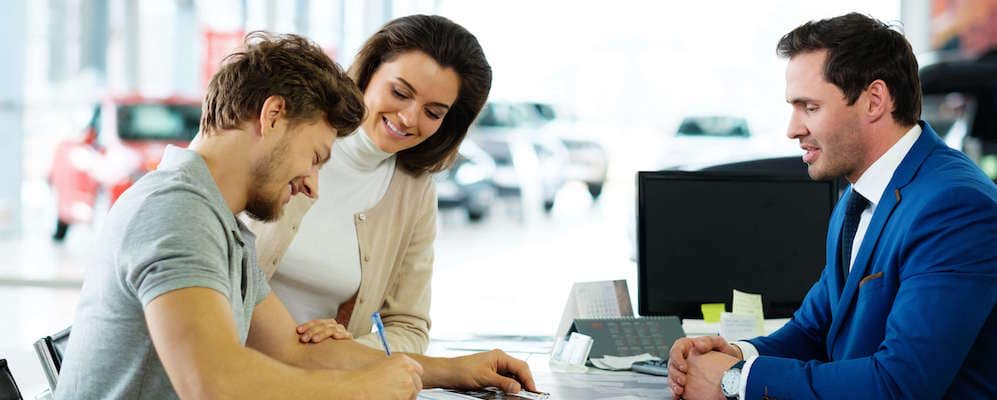 Young couple signs documents at salesman's desk
