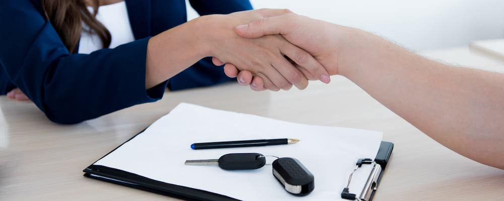 Customer and car seller shaking hands