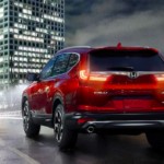 Red 2019 Honda CR-V driving at night in big city