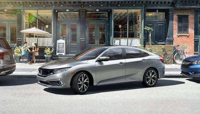 Silver 2019 Honda Civic pulling out of parallel parking spot in city