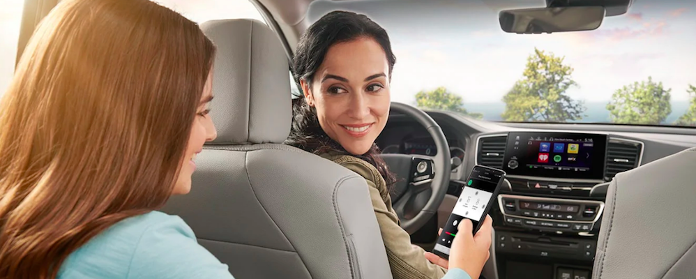 Mom turning around to talk to her daughter sitting in 2nd row of Honda Pilot
