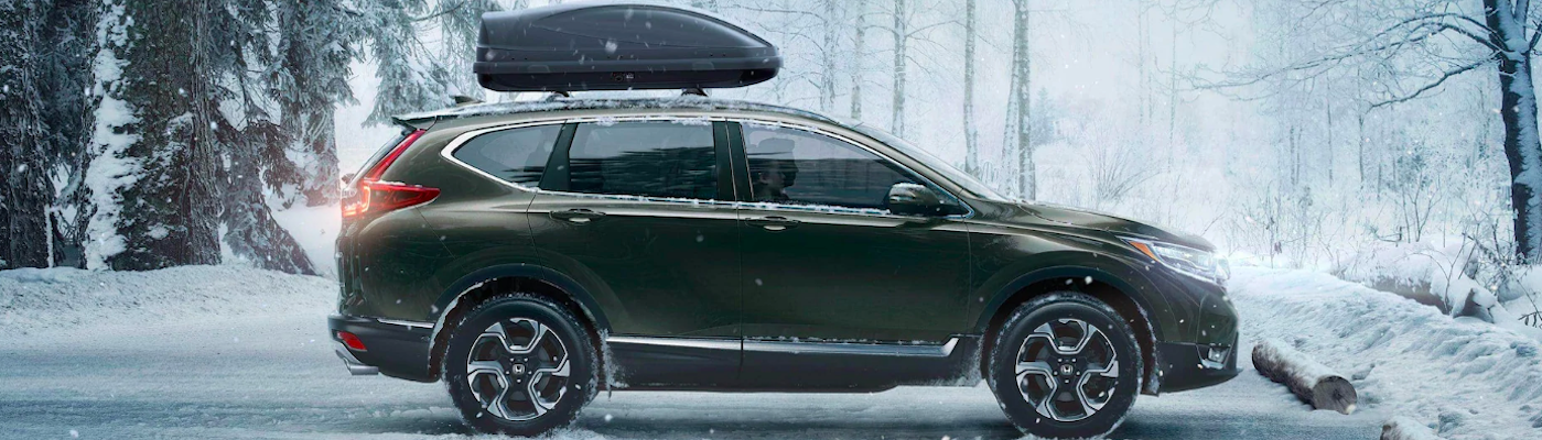 Honda CR-V with roof rack accessory parked in snowy parking lot near woods