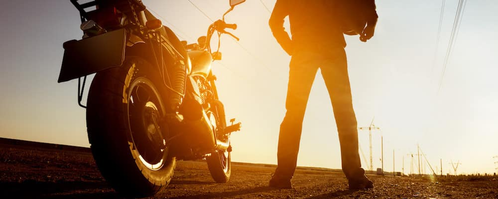 Biker with motorcycle watching the sunset