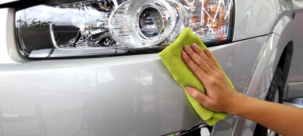 Hand with a cloth polishing a car