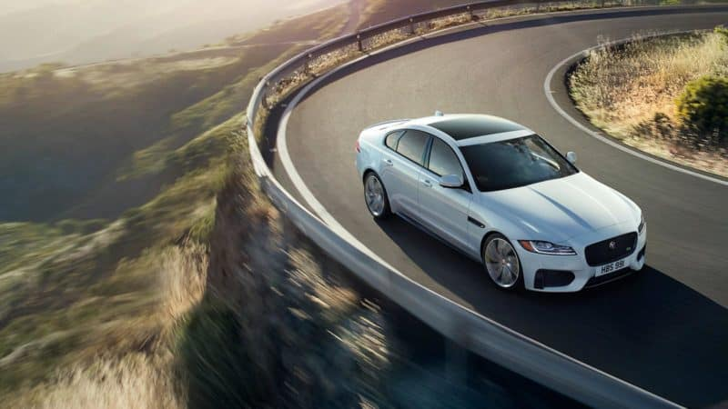 Jaguar XF driving around cliffside