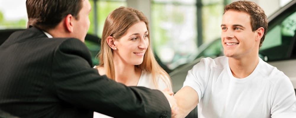 Couple handshaking businessman