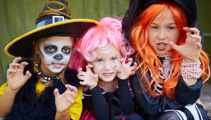 Three young girls in Halloween costumes posing for camera