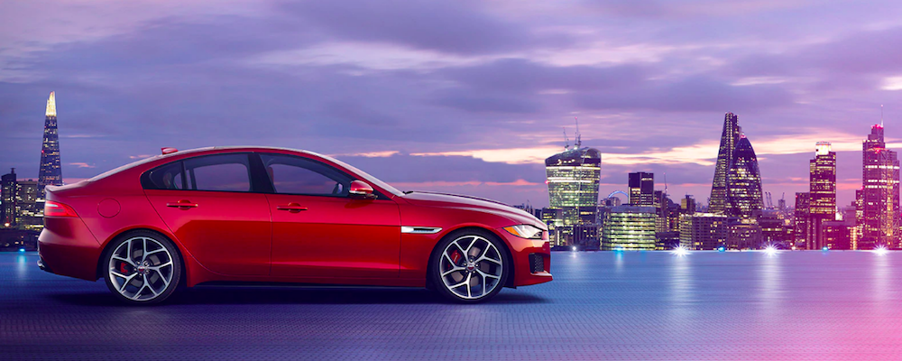 Red Jaguar XE parked on roof of city building with skyline at dusk in background