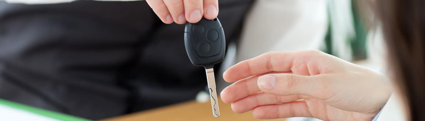 Car salesman handing car keys to customer