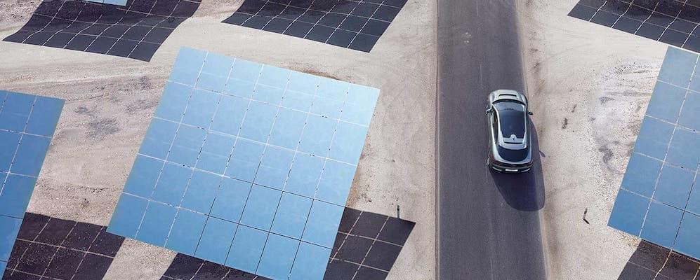 Jaguar I-PACE driving down desert highway near solar panels