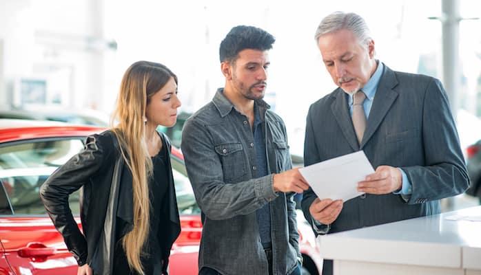 Man and woman talking to car salesman about financing plan