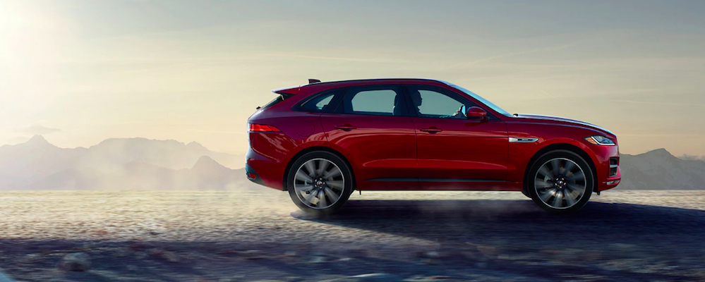 Profile of red 2020 Jaguar F-PACE driving on icy road